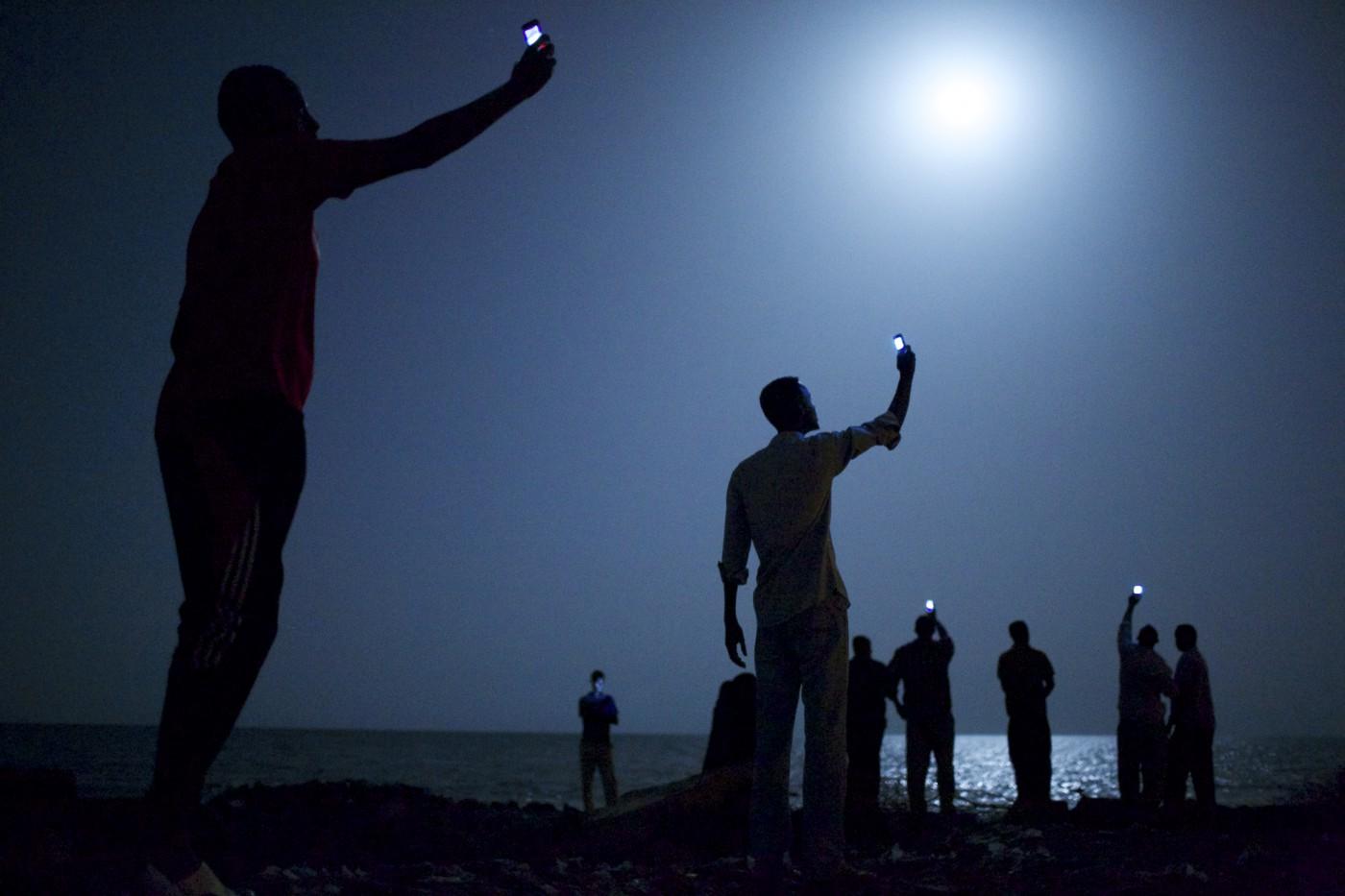 (Kuva: John Stanmeyer, VII/National Geographic) World Press Photo 2013 -kisan voittajakuvassa afrikkalaiset yrittävät saada kännyköihinsä halvempaa  signaalia naapurimaasta,